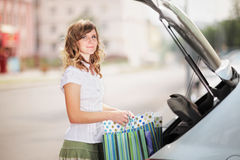 Young caucasian woman standing near an open car trunk with shopping bags. Royalty Free Stock Image
