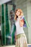 Young caucasian woman standing near a shop window with shopping bags. Stock Photos
