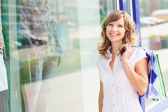 Young caucasian woman standing near a shop window with shopping bags. Royalty Free Stock Photography