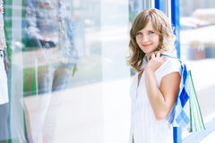 Young caucasian woman standing near a shop window with shopping bags. Stock Photography