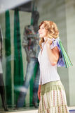 Young caucasian woman standing near a shop window with shopping bags. Royalty Free Stock Images