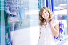 Young caucasian woman standing near a shop window with shopping bags. Royalty Free Stock Photos