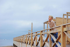 Young caucasian woman standing in a pavilion on the sea shore leaning over railing Stock Images