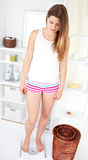 Young caucasian woman standing on a scale at home Royalty Free Stock Image