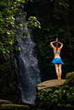 Young Caucasian woman standing on stone, meditating, practicing yoga at waterfall in Ubud, Bali, Indonesia stock images