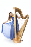Young caucasian woman stands with concert harp in studio against Royalty Free Stock Image