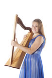 Young caucasian woman stands with small harp in studio against w Royalty Free Stock Photo