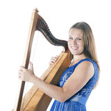 Young caucasian woman stands with small harp in studio against w Stock Photo