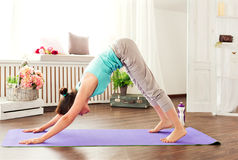 Young caucasian woman staying in a pose on the mat downward dog. Yoga exercises. Stock Images