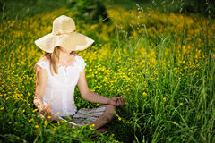 Young Caucasian woman in straw summer hat meditating on nature, sitting in the grass in the park. Royalty Free Stock Image