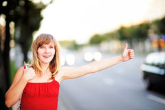 Young caucasian woman on the street hitchhiking Stock Images