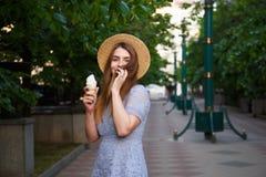 Young caucasian woman in summer hat enjoying the ice cream. Young caucasian woman in summer hat enjoying the ice cream Royalty Free Stock Photos
