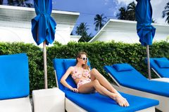 Young Caucasian Woman Relaxing on Sunbed. Young Caucasian Woman in Sunglasses Relaxing on Sunbed Stock Photos