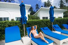 Young Caucasian Woman Relaxing on Sunbed. Young Caucasian Woman in Sunglasses Relaxing on Sunbed Royalty Free Stock Photo