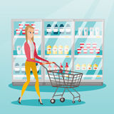 Young caucasian woman with supermarket trolley. Young caucasian woman pushing empty supermarket trolley. Woman shopping in the supermarket with trolley. Woman Royalty Free Stock Photos