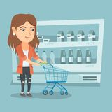 Young caucasian woman with a supermarket trolley. Young caucasian woman pushing an empty supermarket trolley. Woman shopping in the supermarket with a trolley Stock Photography