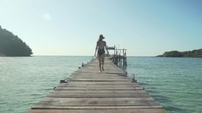 Woman runs on wooden jetty on tropical beach. Young caucasian woman in swimsuit and straw hat happily runs along wooden jetty pier on tropical island beach on stock video footage