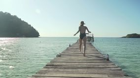 Woman walks on wooden jetty on tropical beach. Young caucasian woman in swimsuit and straw hat happily walks along wooden jetty pier on tropical island beach on stock footage