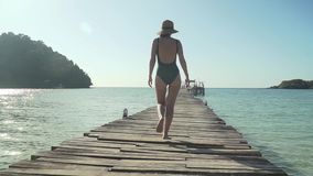 Woman walks on wooden jetty on tropical beach. Young caucasian woman in swimsuit and straw hat happily walks along wooden jetty pier on tropical island beach on stock video