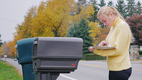Young caucasian woman takes the mail from the mailbox. Countryside in USA stock video footage