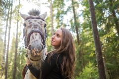 Young caucasian woman taking care of her horse, walking in forest. stock photography