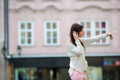 Young caucasian woman taking self portrait in european city. Young caucasian woman sending message and taking self portrait in outdoor cafe at european city Royalty Free Stock Photo