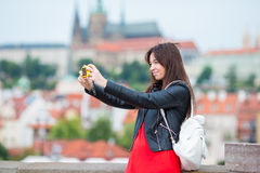 Young caucasian woman taking self portrait in european city. Young caucasian woman sending message and taking self portrait in outdoor cafe at european city Royalty Free Stock Images