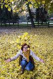Young caucasian woman throwing yellow leaves Royalty Free Stock Images