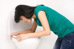 Young caucasian woman in toilet - pregnant, drunk or illness concept. Royalty Free Stock Photography