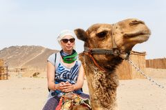 Young caucasian woman tourist riding on camel Royalty Free Stock Photos