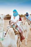 Young caucasian woman tourist riding on camel in Sahara desert Stock Photography