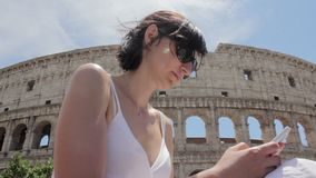 Young caucasian woman tourist texting on beautiful view of european ancient city with mobile smart phone stock footage