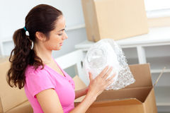 Young caucasian woman unpacking boxes with glasses Royalty Free Stock Images