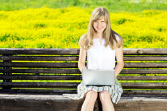 Young Caucasian woman using Laptop on nature, sitting on park bench in the park. Looking at camera Royalty Free Stock Photo