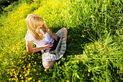 Young Caucasian woman using Laptop (Netbook) on nature, sitting in the grass in the park. Royalty Free Stock Photos