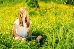 Young Caucasian woman using Laptop (Netbook) on nature, sitting in the grass in the park. Stock Photography