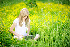 Young Caucasian woman using Laptop (Netbook) on nature, sitting in the grass in the park. Royalty Free Stock Photography