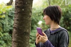 Young woman using smartphone in the forest. Navigation concept. Young Caucasian woman using smartphone in the forest. Navigation concept royalty free stock image