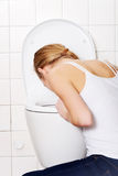 Young caucasian woman is vomiting in the bathroom. Royalty Free Stock Image