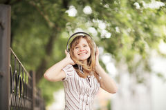 Young Caucasian Woman Walking On The Street And Listening To The Music Using Big Headphones. Royalty Free Stock Photography
