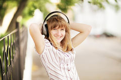Young caucasian woman walking on the street and listening to the music using big headphones. Royalty Free Stock Images