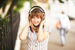Young caucasian woman walking on the street and listening to the music using big headphones. Stock Images