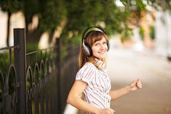 Young caucasian woman walking on the street and listening to the music using big headphones. Stock Photos