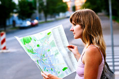 Young caucasian woman walking on the street and looking at map. Stock Photos