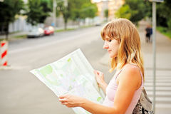 Young caucasian woman walking on the street and looking at map. Royalty Free Stock Photo