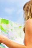 Young caucasian woman walking on the street and looking at map. Stock Photography