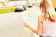 Young caucasian woman walking on the street and looking at map. Stock Photo