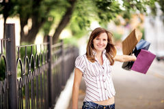 Young caucasian woman walking on the street with shopping bags. Stock Photos