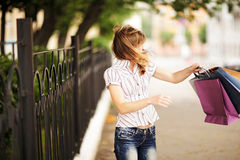 Young caucasian woman walking on the street with shopping bags. Stock Images