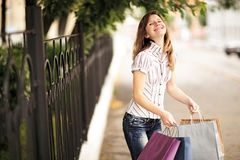 Young caucasian woman walking on the street with shopping bags. Royalty Free Stock Photo